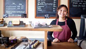 Servitris som ler vid Gunnebo Cafés disk
