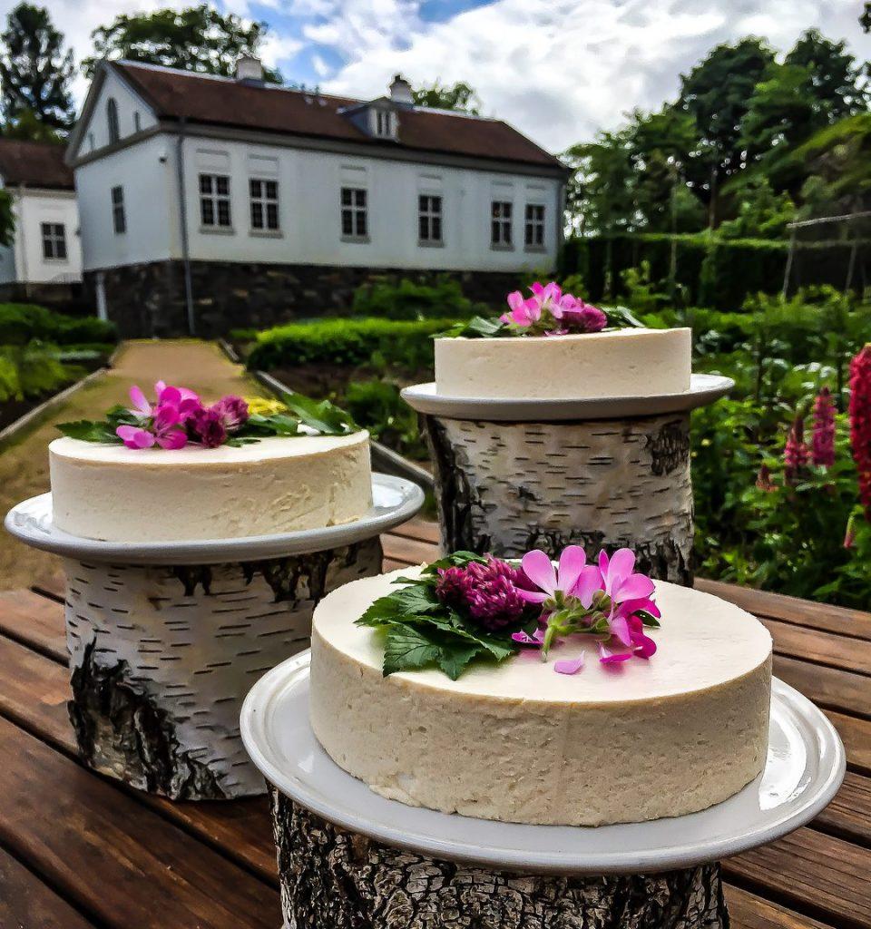 Tre vita bröllopstårtor dekorerade med rosa blomster uppställda på trästockar i olika nivåer.