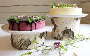 En lila och en gul tårta vackert dekorerade med glasyr och blomster.