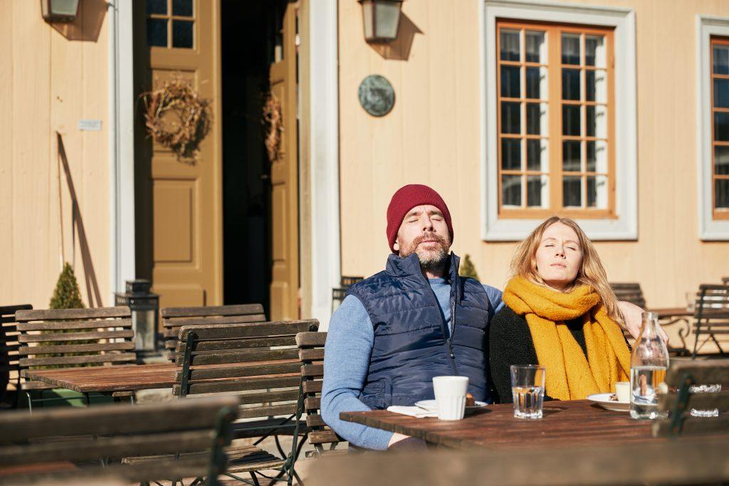 Man och kvinna som solar på Gunnebo Cafés uteservering