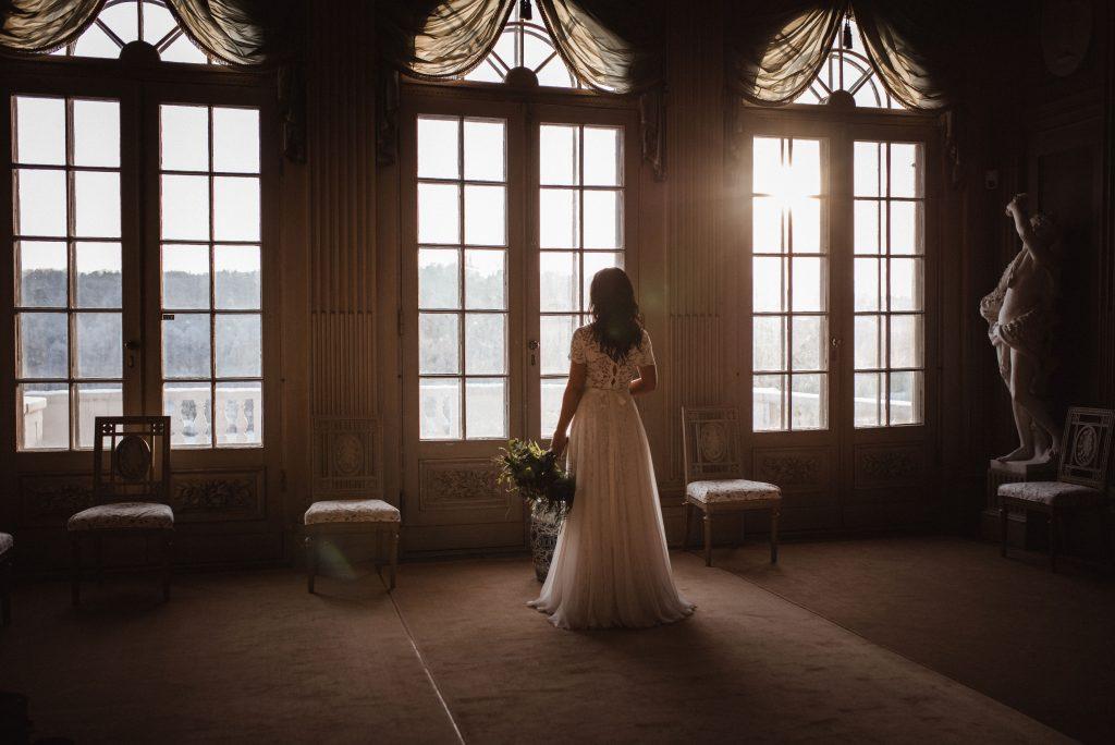 brud som står i Gunnebo Slotts bröllopslokal och blickar ut genom fönstret.