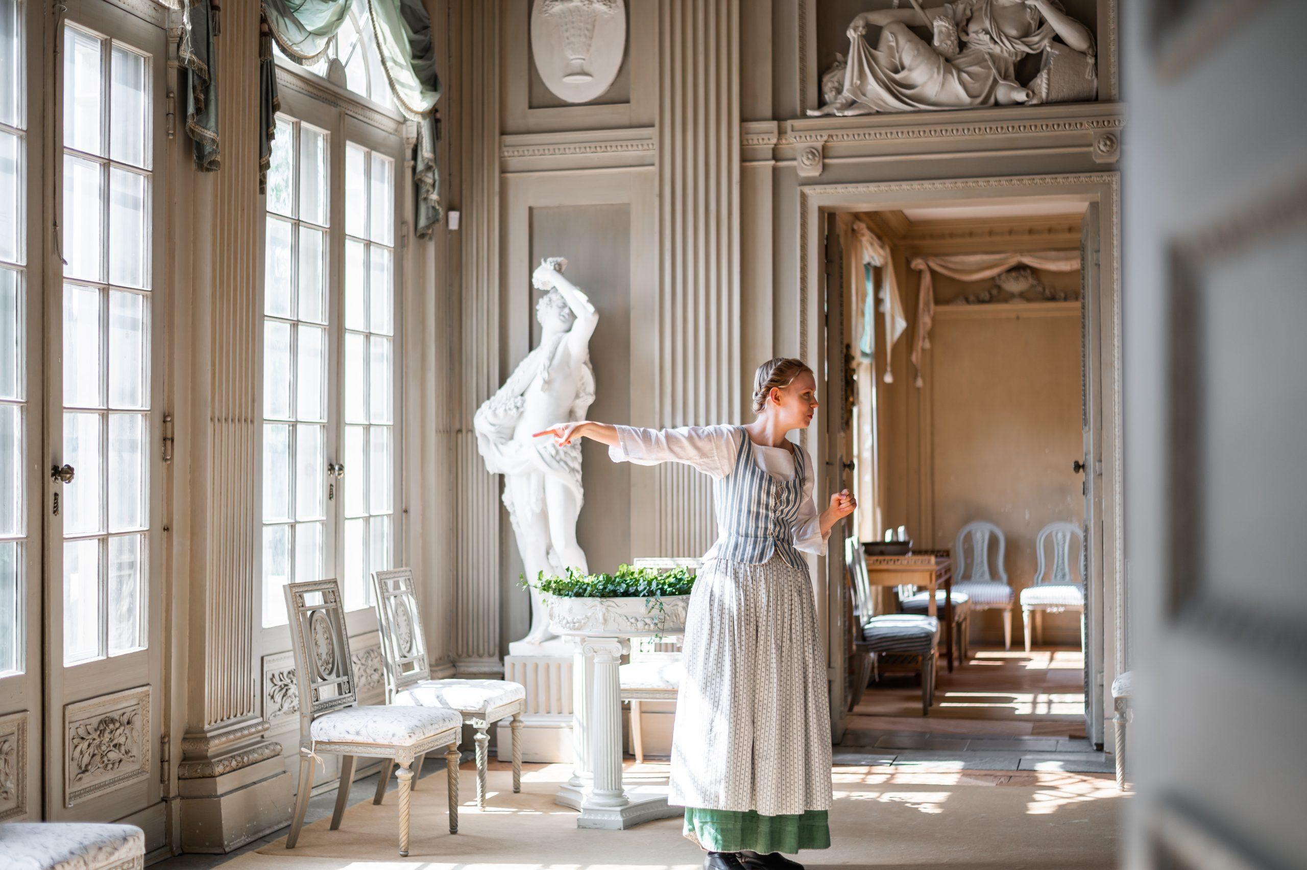 kvinna visar slottet i tidsenlig klädsel