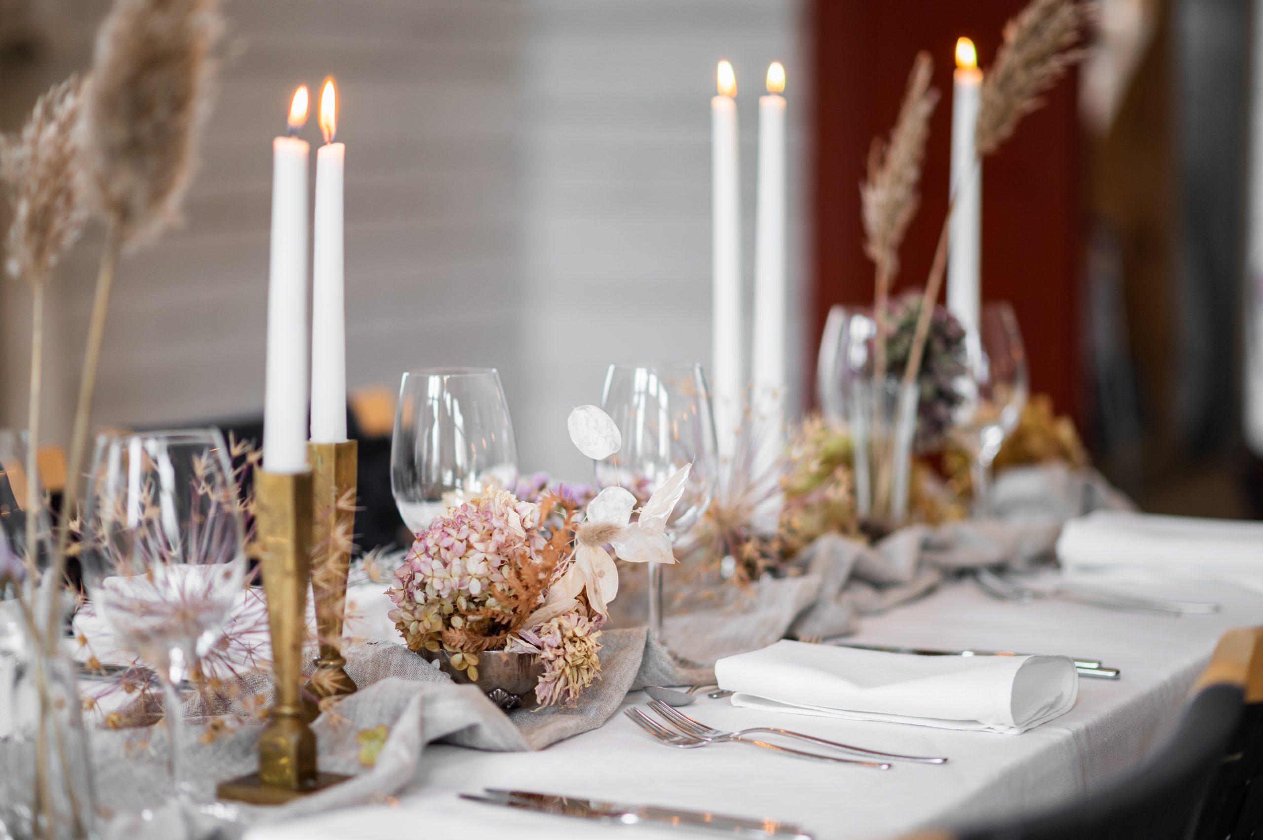 uppdukat bord med levande ljus och torkade blommor