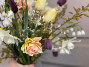 Hand som håller en bukett med vackra blommor.